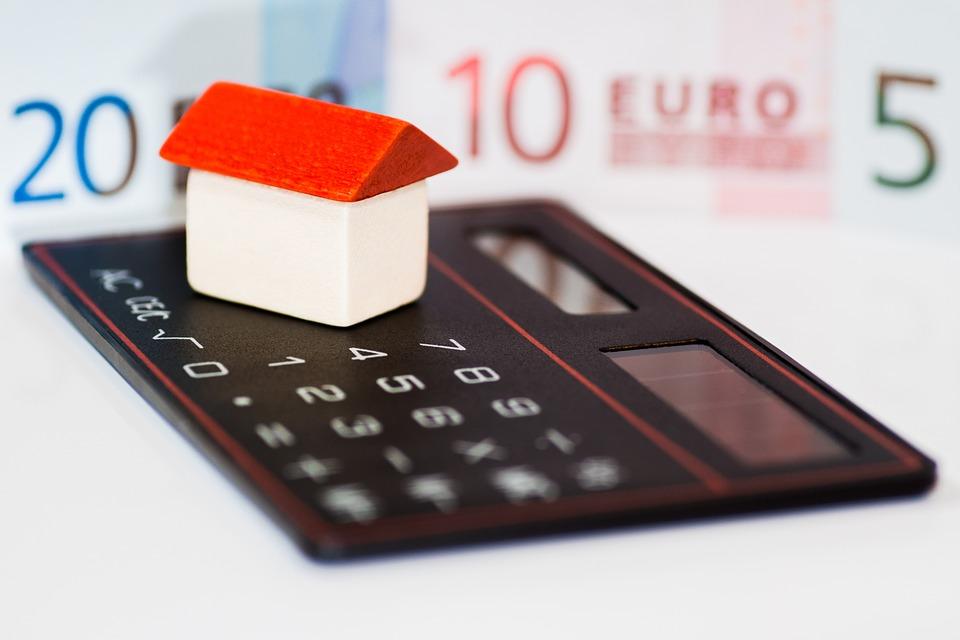 Petite maison en bois posée sur une calculatrice pour estimer la plus-value à la revente