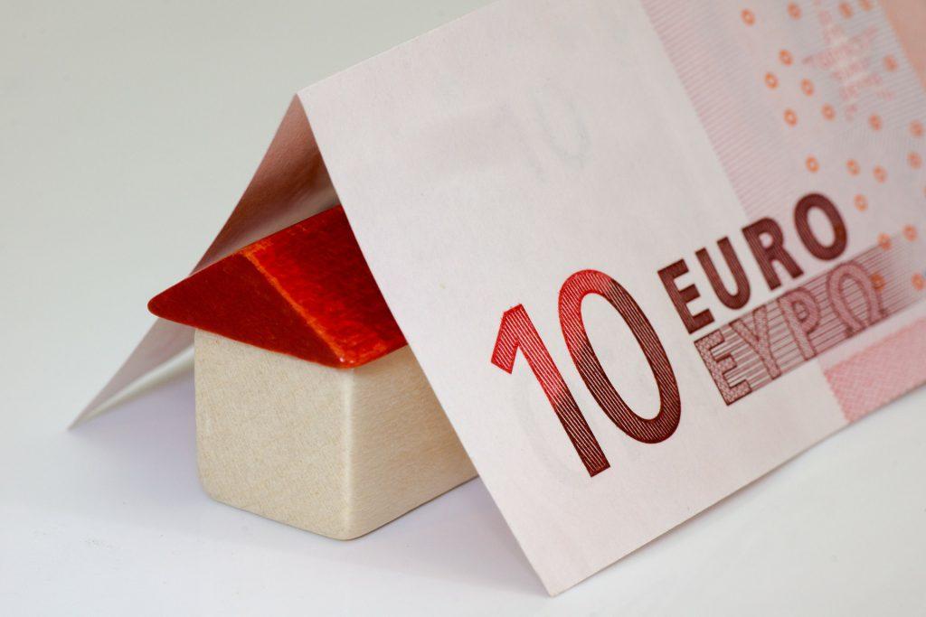 Maison miniature en bois avec un toit rouge sous un billet de 10 euros